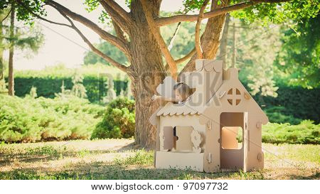 girl playing in cardboard house at city park