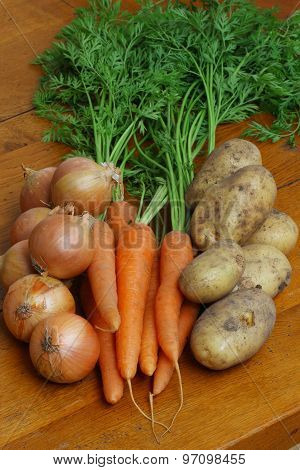 Onions, Carrots & Potatoes on a Wooden Kitchen Table