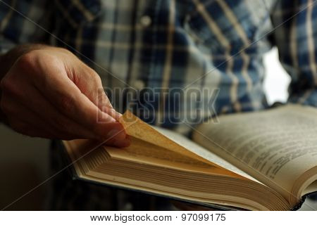 Young man reading book close up
