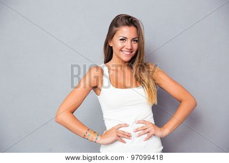 Happy attractive girl standing over gray background and looking at camera