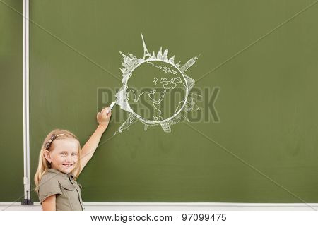 Cute girl of school age writing with chalk on blackboard