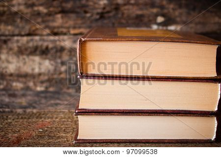 Three Brown Books In A Stack Vertically On A Wooden Background