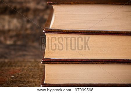 Three Brown Books In A Stack Vertically On Wooden Background Close-up Page