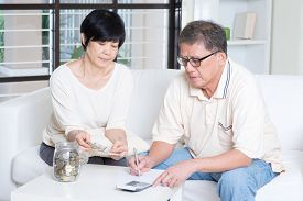 stock photo of family planning  - Asian senior couple counting on money - JPG