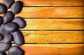 foto of drop oil  - Black stones with water drops on the left side on wooden slats - JPG
