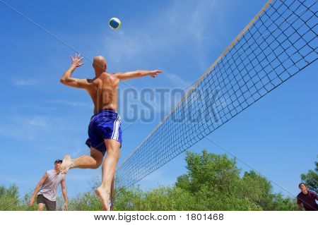 Three Men Playing Beach Volleyball - Balding Man Moves Muscular Shoulder Back To Hit The Ball