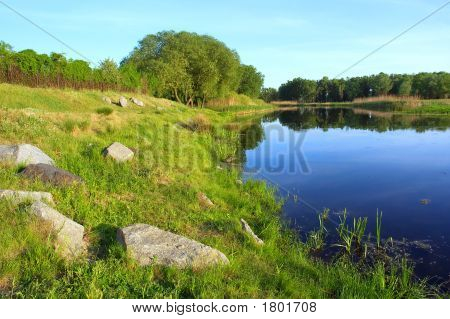 Beautiful Spring Lake With Stones And Trees On Shore - In Sunset Light
