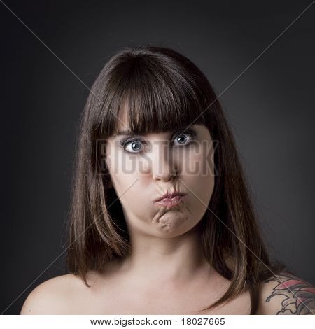 Portrait of a beautiful and funny woman with cheeks full of air against a grey background