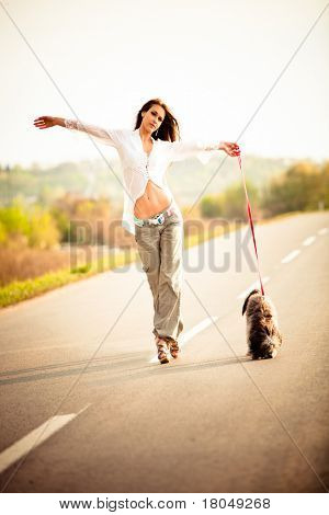 young woman open arms walking with dog on the road, summer day sunset
