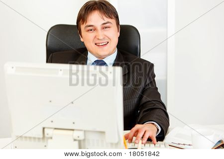 Smiling modern businessman sitting at office desk and working on pc