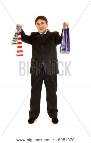 Full length portrait of smiling young businessman holding shopping bags isolated on white