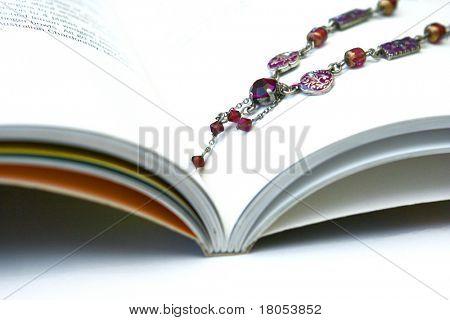 Ein wunderschönes braun und violett Perlen Collier-Ort auf ein geöffnetes Buch