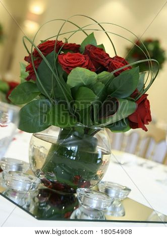 A pretty table centerpiece made out of red roses and bear grass in a vase placed on a mirror