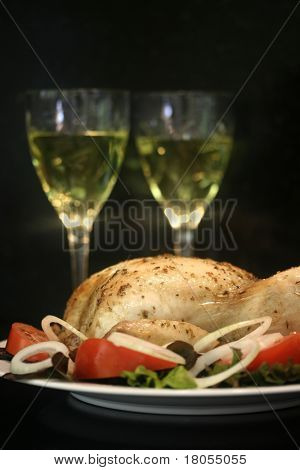 A plate of roast chicken arranged beautifully on a bed of fresh salad, with two wine glasses with black background- isolated