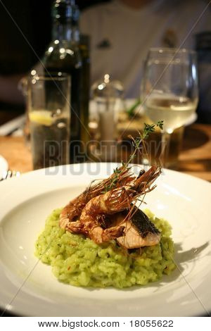Close up of grilled prawn and salmon risotto, a bottle of white wine