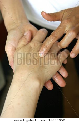 A massage therapist giving a hand massage to a client