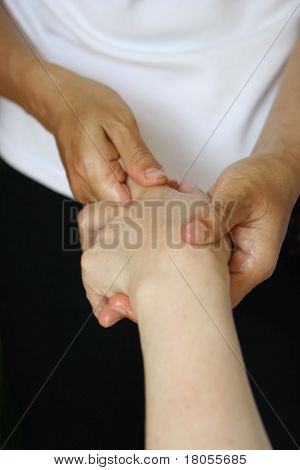 A lady receiving a hand massage as part of a holistic massage treatment
