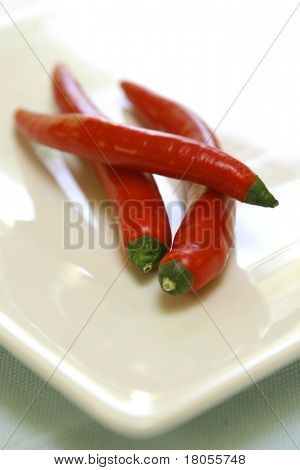 Three slender red chillies arranged on white plate