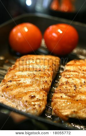 Two pan seared salmon with two whole tomatoes