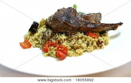 A plate of grilled vegetable couscous with lamb chops, isolated on white