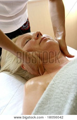 A lady masseur giving a neck massage to her client . ( Suitable for spa image )