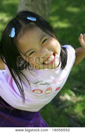 A young Vietnamese girl plays happily in the park