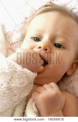 Beautiful baby girl playing with her fingers and pink blanky