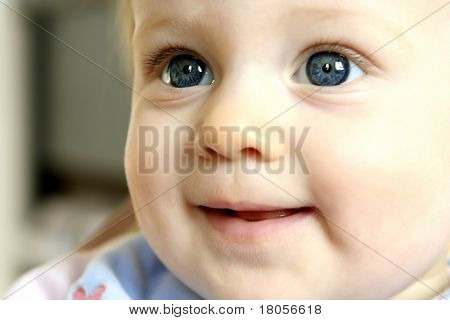 Baby girl with big clear blue eyes playing happily
