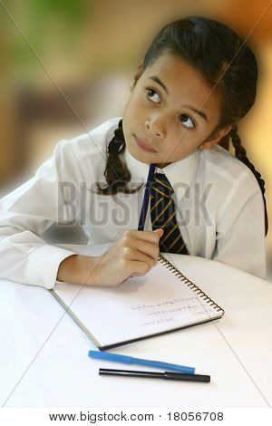 A young girl ponders hard as she attempts at her homework.
