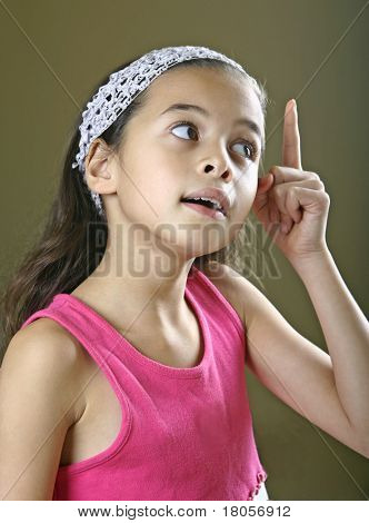 A young girl struck with an idea, wide eyed with index finger pointing above.
