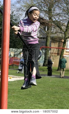 A young girl being thrown in the air from the force of the playground swing.