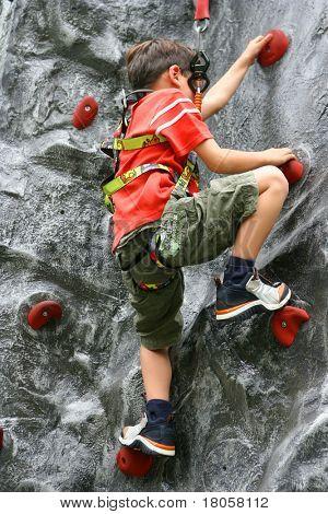 Young boy climbing up the indoor rockclimbing wall.