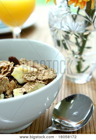 Bowl of bran cereal with banana chips and raisins for breakfast with a glass of orange juice.