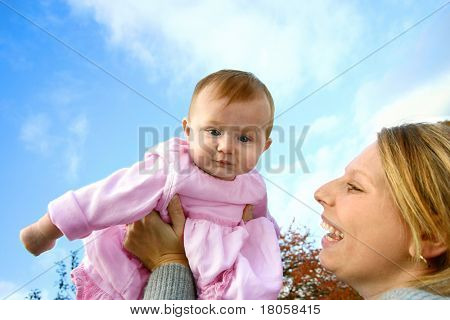 Young mom lifts her baby girl up high in the air, outdoor