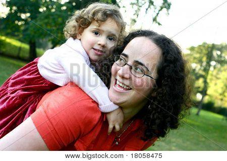 A little girl having a piggyback ride on her mom, enjoying the park