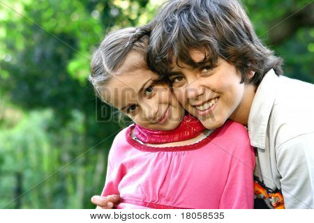 Beautiful girl with her older brother outdoor in the park