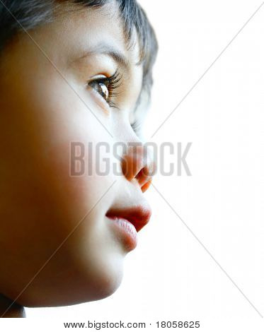 Little toddler boy looks out far, curious about the world around him.