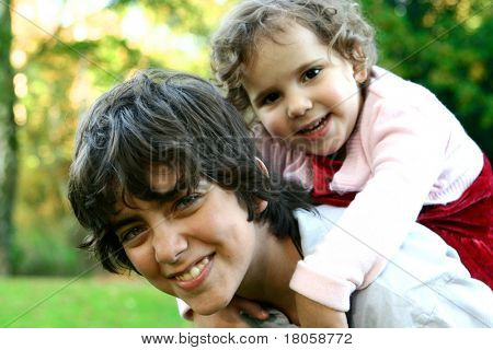 Young boy carrying his toddler sister on his shoulder, enjoying time in the park
