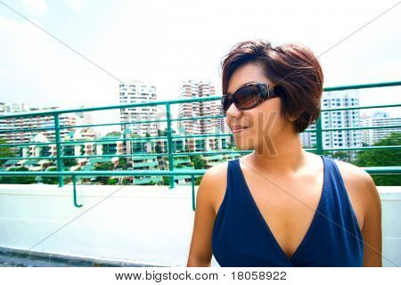 Young Asian female on top of roof terrace looking down onto the apartments in the valley, in a tropical country.