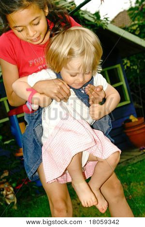 Young girl having fun playing with a 2 year old female toddler in a bouncing game, outdoor in the garden