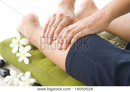 Lady masseur giving patient a leg massage