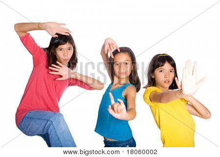 Three happy girl friends in funny kungfu poses having fun with each other.