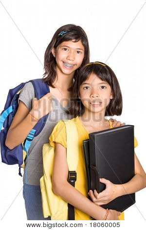 Two young girls ready to attend school with their rucksack and folders of notes.