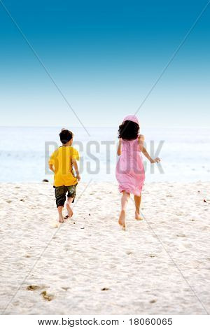 Excited brother and sister running on soft sandy beach towards the sea