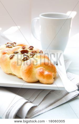 A piece of delicious sweet raisin twisted bun with sugar sprinkling and cinnamon served with cup of coffee for an enjoyable early morning breakfast or snack.