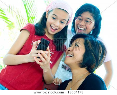 Young girls happy and laughing while sharing an information on a cellphone