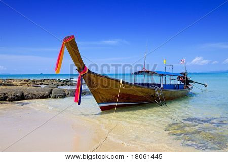 Lone tailboat floating in the clear waters of the Andaman sea against beautiful clear blue sky
