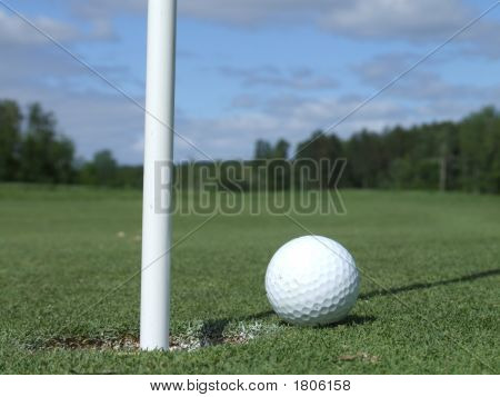 Golf Ball Next To Hole