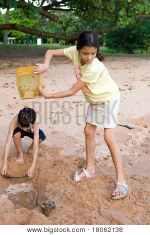 Young girl  pouring water in hole as younger brother digs it deeper