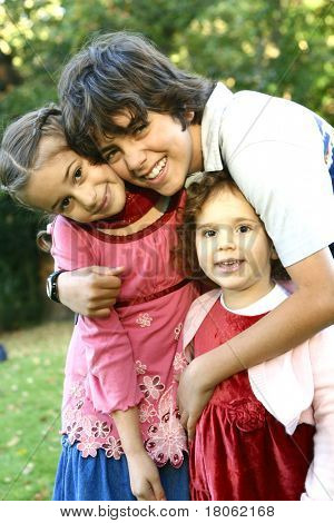 Elder brother holding close to his two younger sister, in the park